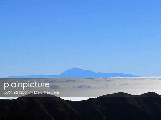 Aerial view mountain against blue sky above clouds, Santa Cruz de La Palma, Spain - p301m2123047 by Marc Peschke