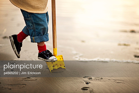 Preschool age boy playing with a spade in the sand at the beach - p4565202 by Jim Erickson