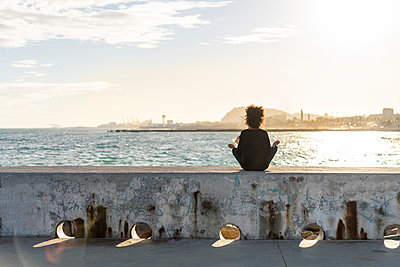 Spain, Barcelona, back view of  woman sitting on wall in front of the sea meditating - p300m2068335 von VITTA GALLERY