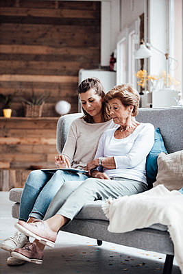 Young woman using digital tablet while sitting by grandmother on sofa at home - p300m2274908 by Gustafsson