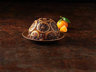 Christmas pudding decorated with sliced oranges - p429m839182 by Diana Miller