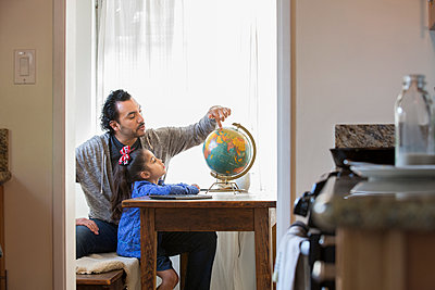 Hispanic father and daughter examining globe - p555m1312283 by Sam Diephuis