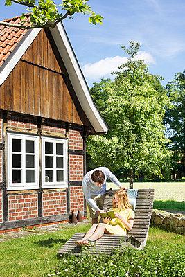 Paar mit Buch im Garten - p606m919180 von Iris Friedrich