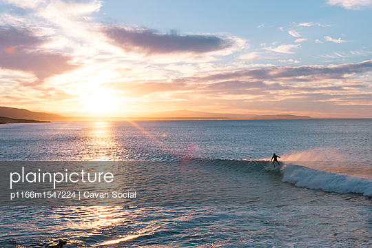plainpicture | Photo library for authentic images - plainpicture p1166m1547224 - Man surfing in sea against ... - plainpicture/Cavan Images/Cavan Social