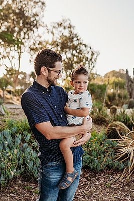 Portrait of dad holding toddler boy and looking at him in sunny garden - p1166m2136618 by Cavan Images