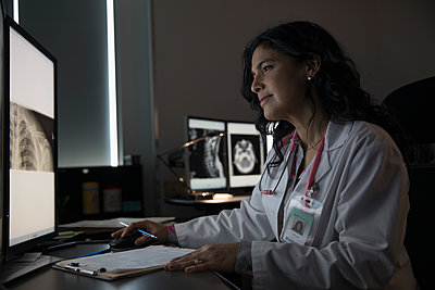 Focused female doctor reviewing digital x-ray on computer in dark clinic doctor - p1192m1212972 by Hero Images