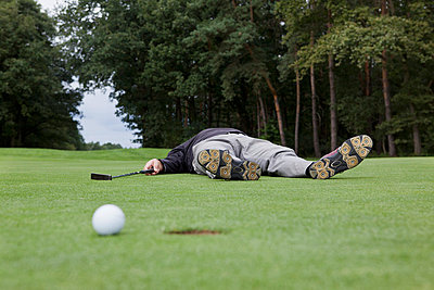 A distraught golfer lying on putting green with ball at the edge of hole - p30119780f by Halfdark