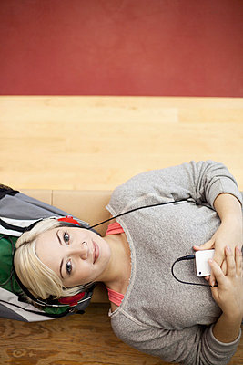 Pretty college student listening to music. - p328m729838f by Hero Images