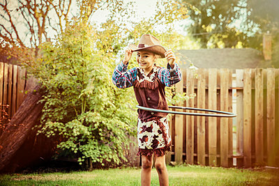 Mixed race girl in cowboy costume spinning plastic hoop in backyard - p555m1412568 by Inti St Clair