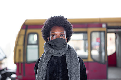 Young dark-skinned woman in front of a bus, portrait - p975m2247764 by Hayden Verry