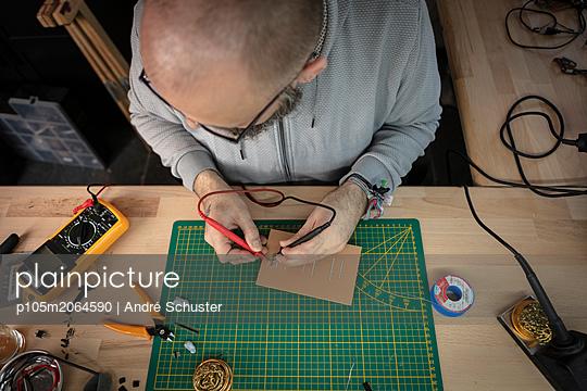 Elektriker prüft die Spannung auf einer Platine - p105m2064590 von André Schuster