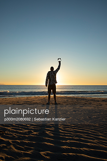 Man with headphones and sunglasses at the beach - p300m2080692 by Sebastian Kanzler