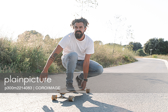 Handsome bearded mature man skateboarding on road against clear sky - p300m2214083 by COROIMAGE