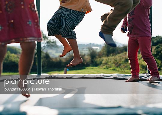 Kinder springen auf dem Trampolin - p972m1160351 von Rowan Thornhill