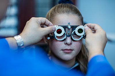 Girl doing eye test at optometrist - p300m1189435 by zerocreatives