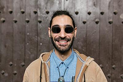 Smiling hipster man standing in front of door - p300m2277730 by Xavier Lorenzo
