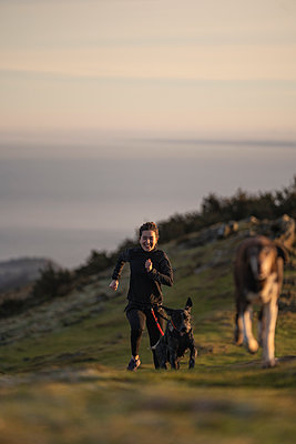 Young woman running with dogs in canicross style - p300m2282817 by SERGIO NIEVAS