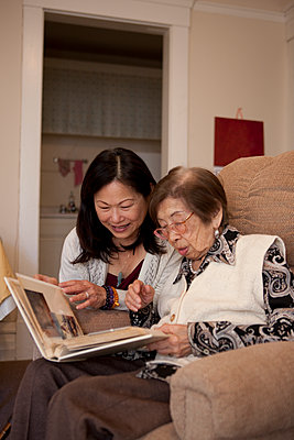 Asian mother and daughter looking at photo album - p555m1408842 by Shestock