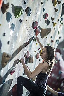 Athlete climbing rock wall in gym - p555m1411958 by John Fedele