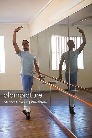Ballerino practicing ballet dance at barre - p1315m1514533 by Wavebreak