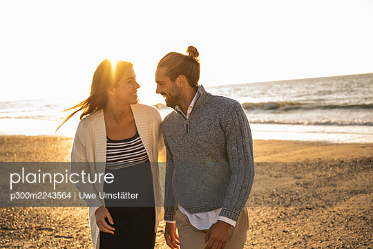 Happy young couple at beach against clear sky during sunny day - p300m2243564 by Uwe Umstätter