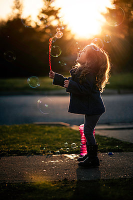 Full length of playful girl playing with bubbles on footpath during sunset - p1166m1509120 by Cavan Images