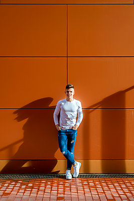Front view young man leaning on a wall while looking camera - p1166m2095938 by Cavan Images
