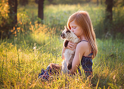 Young Girl With Kitten Outside in Meadow - p1166m2147108 by Cavan Images