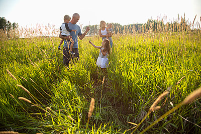 Young family in sunny, rural field - p1192m2047608 by Hero Images