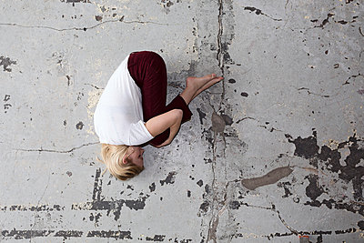 Woman lying in fetal position on the floor - p1301m1582537 by Delia Baum