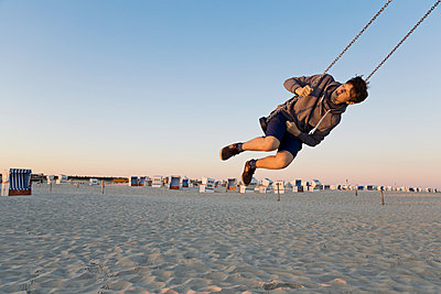 Germany, St Peter-Ording, teenager swinging on a swing at the beach - p300m1052954f by Merle M.