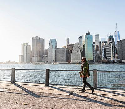 USA, Brooklyn, businessman with briefcase walking in front of Manhattan skyline - p300m1205096 by Uwe Umstätter