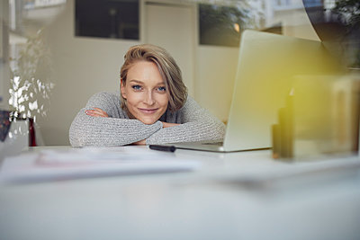 Portrait of smiling young woman leaning on desk with laptop - p300m2012934 by Philipp Nemenz