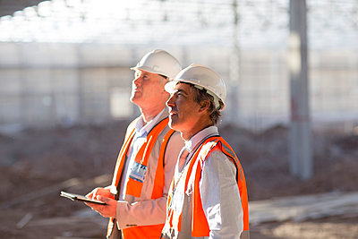 Caucasian architects using digital tablet at construction site - p555m1411761 by Resolution Productions