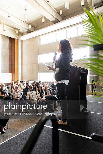 Businesswoman with microphone and digital tablet leading conference presentation - p1192m2123183 by Hero Images