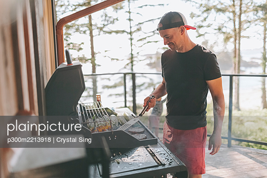 Man cooking on barbecue while standing at patio - p300m2213918 by Crystal Sing