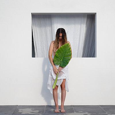 Naked woman hiding behind huge green leaf - p1105m2200701 by Virginie Plauchut