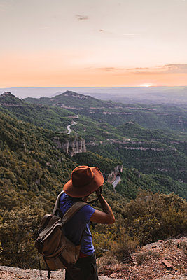 Spain, Barcelona, Montserrat, man with backpack taking photo of view at sunset - p300m2041576 von VITTA GALLERY