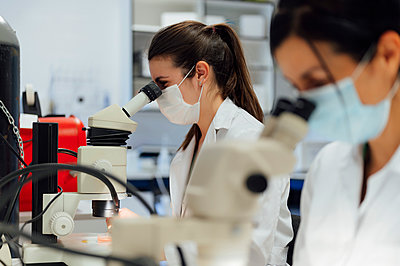 Female scientists looking through microscope while examining medical samples in laboratory during pandemic - p300m2286781 by Miguel Angel Partido Garcia