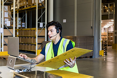 Confident young male customer service representative using laptop while sitting with package at desk in warehouse - p426m2018811 by Maskot