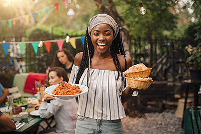 Portrait of smiling young woman carrying food while standing in backyard during garden party - p426m2046169 by Maskot
