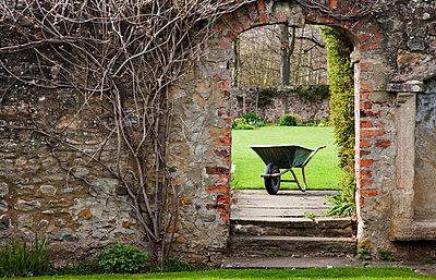 A wheelbarrow as seen through an opening in a stone wall; yorkshire england - p442m700158f by John Short