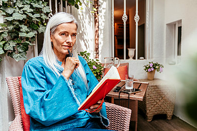 Musing older person with manuscript on the terrace - p608m2203553 by Jens Nieth