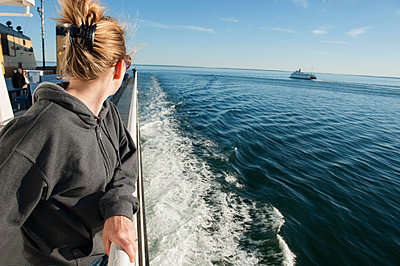 Woman standing on deck of ferry boat, looking over shoulder at view - p623m1086471f by Jerome Gorin