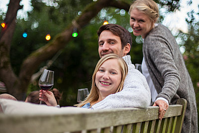 Freunde trinken Rotwein auf einer Gartenparty - p788m1165281 von Lisa Krechting