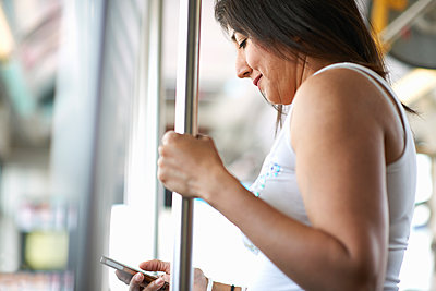 Woman standing on bus reading smartphone texts, Los Angeles, California, USA - p924m1135987f by Peter Muller