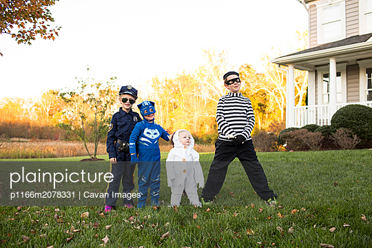 Four Siblings in Halloween Costumes in Front of House at Sunset - p1166m2078331 by Cavan Images