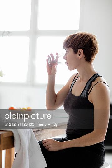 Junge Frau nach dem Yoga am Tisch - p1212m1123403 von harry + lidy