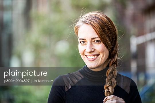 Portrait of smiling woman with braid - p300m2004527 von Jo Kirchherr