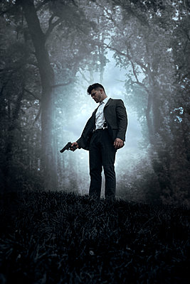 Man with Suit and Gun in Woods  - p1248m2134701 by miguel sobreira